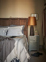 Double bed with oak headboard and lamp on bedside cabinet