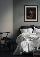 Nude painting on wall above double bed and classic chair in bedroom with grey walls