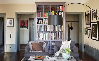 Grey armchairs, coffee table and arc lamp in front of bookcase