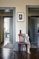Black-and-white photo on wall above chair placed between two door frames