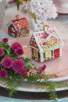 Christbaumanhänger in Form eines Lebkuchenhauses auf dem Teller