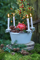 Advent arrangement with candle clips on edge of enamel bowl on moss outside