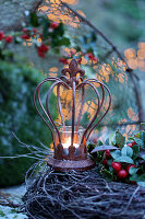 Tealight in rusty decorative crown on top of wreath on table outside