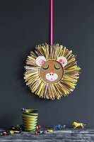 Lion's head made from cardboard and raffia decorating child's bedroom