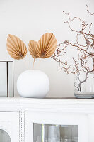 DIY palm leaves made from brown paper in white spherical vase