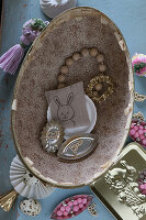 Vintage-style Easter arrangement of knick-knacks in old cardboard egg
