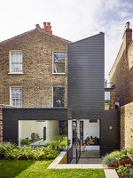 Brick house with modern wood-clad extension and swivelling terrace doors