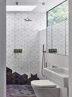 Geometric tiles and transom window above mirror in modern bathroom in white and grey