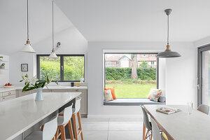 Moderne Wohnküche mit Sitzbank in der Fensternische zum Garten