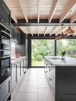 Moderne Küche mit grauen Kassettenfronten und Holzdecke