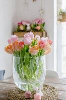 Vase of pink and apricot tulips on table in dining room