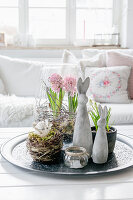 Easter bunny, nest and spring flowers in living room