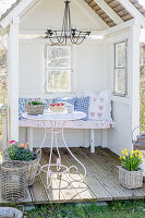 Pretty cushions on bench in arbour with small deck