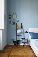 Ladder used as shelf and bedside table against blue wall in bedroom