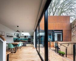 Modernes Architektenhaus mit rostiger Fassade und offenem Wohnraum