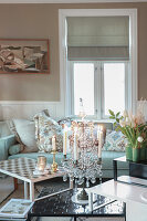 Lit candles in elegant candelabra on coffee table