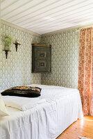 Bett mit weißer Decke und Eckschränkchen im Schlafzimmer mit Tapete