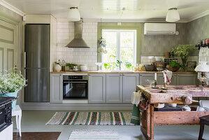 Landhausküche mit grauen Schrankfronten, im Vordergrund antiker Tisch