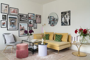 Yellow velvet sofa below gallery of photographs on wall