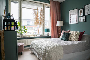 Double bed in guest room with dark matt green walls