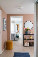 Sideboard below mirror on peach-coloured wall of hallway with view into bedroom
