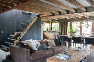Brown sofa in rustic interior with wood-beamed ceiling