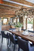 Upholstered chairs around rustic dining table in open-plan country-house kitchen