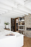 Rustic bedroom with white ceiling beams and stone wall