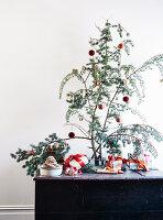 Zweige mit Christbaumkugeln auf einer Truhe mit verpackten Geschenken
