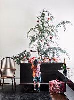 Junge an alter Truhe mit verpackten Geschenken und Nadelzweigen