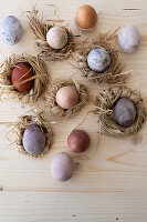 Easter eggs coloured using natural dyes in nests of straw