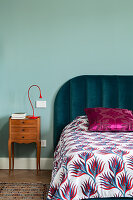 Double bed with patterned bedspread and bedside table against duck egg blue wall