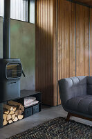 Log burner against concrete wall and grey sofa in open-plan interior