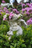 Cherub with flower crown in box bush