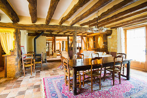 Dining area in open-plan interior with rustic wood-beamed ceiling