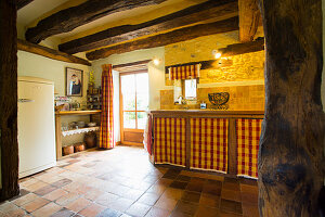 Rustic kitchen with rustic wood-beamed ceiling
