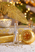 Wish list in tiny bottle surrounded by golden Christmas decorations
