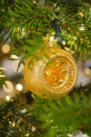 Golden Christmas bauble hanging from branch in front of twinkling lights