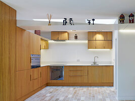 Kitchen with wooden cabinet, stone tiles and skylights