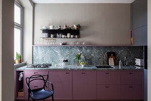 Black chair next to kitchen counter with berry-coloured cabinets