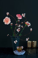 Modern arrangement of carnations and branches of laurustinus flowers with leaves removed