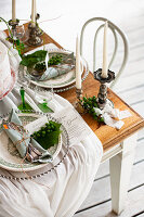 Gathered tablecloth and silver candlesticks on festively set table