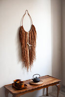 Ethnic-style wall hanging made from raffia threads and ring