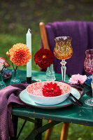 Place setting decorated with dahlias outdoors