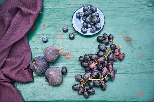 Blueberries, grapes and figs on turquoise wooden table