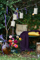 Bench, lanterns and vase of dahlias in romantic ivy-covered arbour
