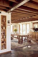 Blick neben eingebautem Küchenregal auf Essbereich mit langem Holztisch
