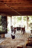 Holzterrasse mit Esstisch und Stühlen, im Vordergrund ein Hahn