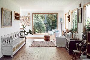 Sitzbereich mit Vintage Holzbank, darüber Kunstwerk und Hussensessel