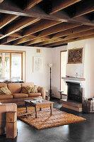 Braunes Sofa und Couchtisch vor Kamin